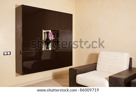 Part of modern interior in warm tones with armchair and niche - stock photo