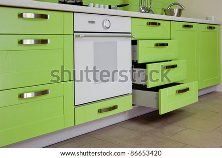 Part of modern kitchen furniture of the green color executed from wood - stock photo