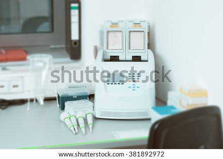 Part of modern scientific laboratory with PCR machine for DNA amplification on work bench. This image is blurred, there is no exact focus here.  - stock photo
