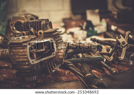Part of motorcycle engine on a table in workshop - stock photo