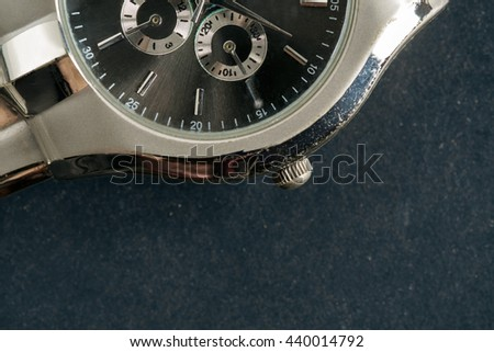 Part of old and dirty wristwatch on black paper background. - stock photo