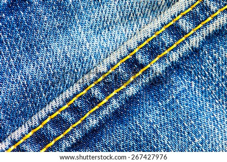part of old blue jeans background with diagonal seams.  - stock photo