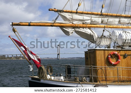 Part of old Danish sailboat and Little Belt Bridge in background. - stock photo
