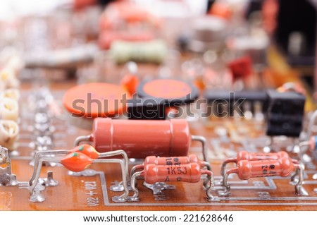 Part of old vintage printed circuit board with electronic components. Closeup with shallow DOF. - stock photo