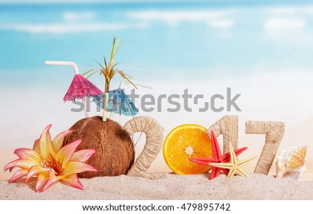 Part of orange instead of the number 0 in the amount of 2017 starfish and sea shell, coconut, flower in the sand against the sea.