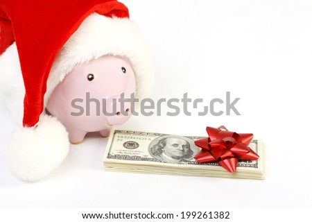 Part of piggy bank with Santa Claus hat and stack of money american hundred dollar bills with red bow standing  on white background - stock photo