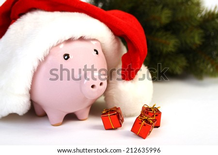 Part of piggy bank with Santa Claus hat and three little gifts and christmas tree standing on white background - stock photo