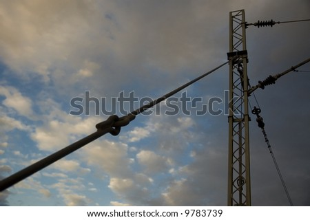 Part of power line with cloudy sky as a background