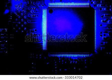 Part of printed circuit board with CPU in dark blue colors. Digital effects applied. - stock photo