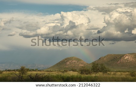 Part of rainbow shows delicate colors below storm clouds over landscape with hills and wild vegetation/Rainbow under Cumulus Clouds in Rural Landscape/Part of rainbow with soft colors over hills - stock photo