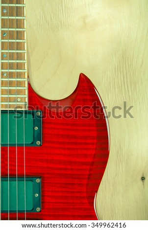 Part of red electric guitar on a wooden background, soft focus - stock photo