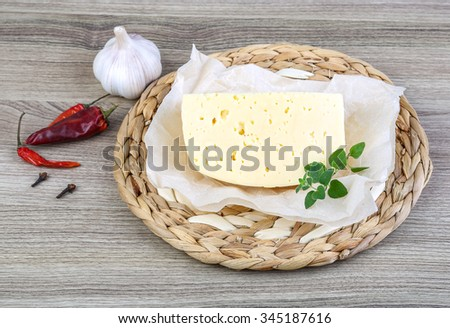 Part of round cheese on the wood background with herbs - stock photo