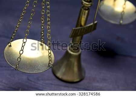 Part of scale or scales of brass on a dark wood showing law justice or legal concept, selected focus and narrow depth of field - stock photo