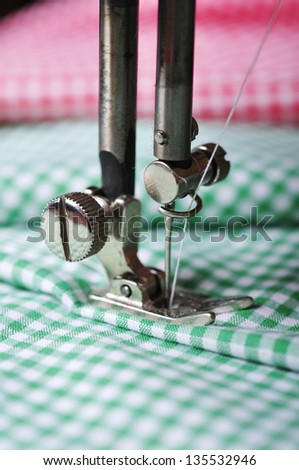 Part of sewing machine and checkered fabric closeup - stock photo
