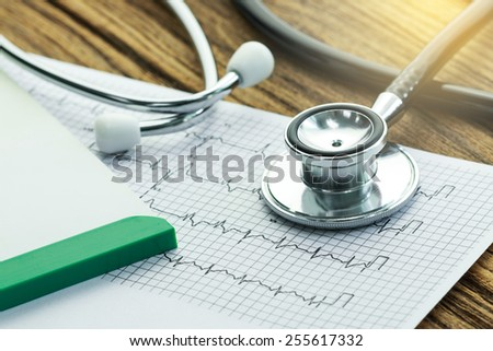 part of stethoscope with cardiogram and medical check-up report for healthcare concept - stock photo