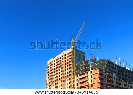 Part of tall crane and building under construction at sunny winter day - stock photo
