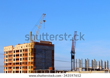 Part of tall cranes and building under construction at sunny winter day - stock photo
