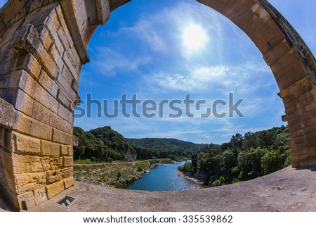 Part of the bridge. One bridge span is photographed lens Fisheye. Three-tiered aqueduct Pont du Gard - the highest in Europe. Provence, spring sunny day - stock photo