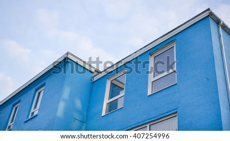 Part of the exterior of a blue building in the UK - stock photo