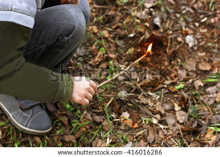 Part of the image of a child who squats in the forest among the dry withered leaves. Child sets fire to the foliage. - stock photo