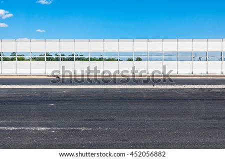 Part of the new highway with noise protection fence along. - stock photo