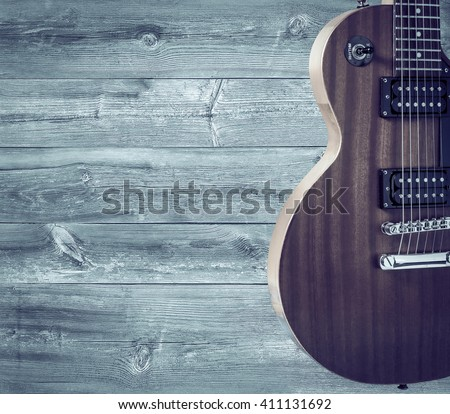 Part of the orange electric guitar on wooden background. A place for writing of the text - stock photo