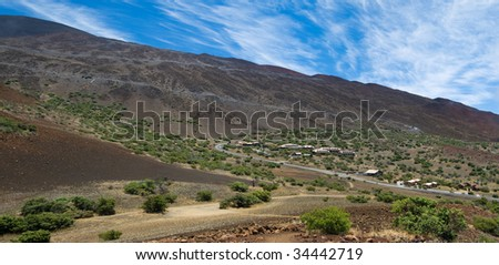 Part of the road leading to the observatories atop Mauna Kea along with the Onizuka Center for International Astronomy Visitor Information Station. - stock photo