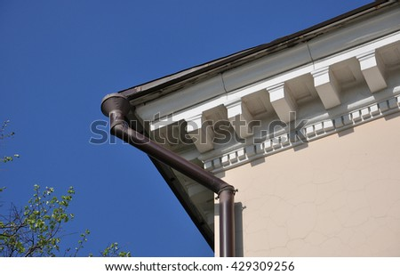 part of the roof of the old house with the drainpipe - stock photo