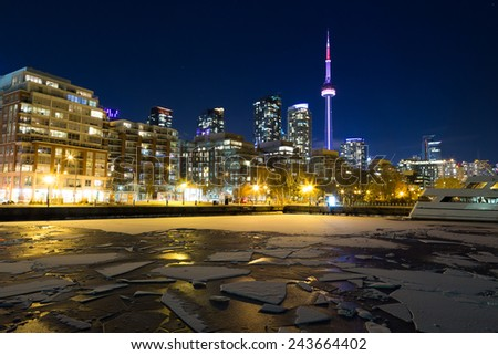 Part of the Toronto Skyline in the winter showing frozen water in the lake