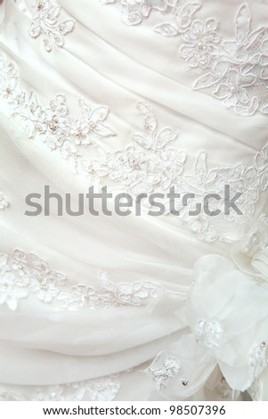 part of the white wedding dress with artificial flowers - stock photo