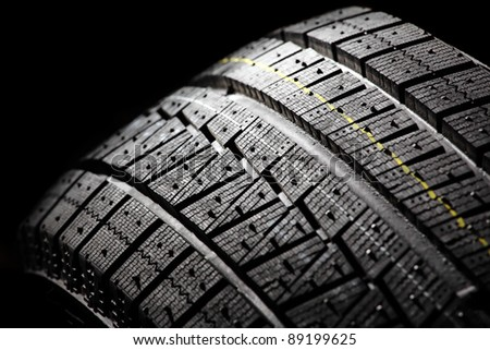 Part of unused winter car tire on a black background.. Horizontal composition. - stock photo