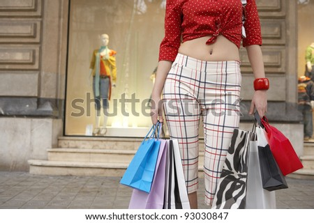 Part view of a young woman holding shopping bags in shopping street. - stock photo