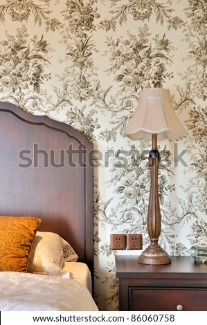Part view of bedroom with flowery wallpaper - stock photo
