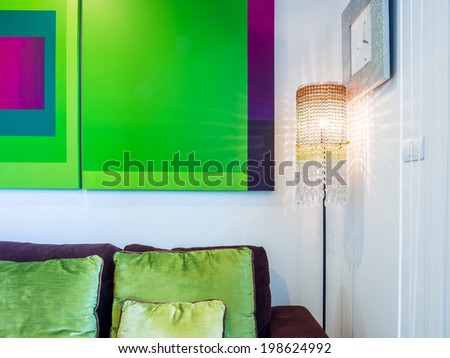 Partial of white minimalist living room with lamp and geometric green painting - stock photo