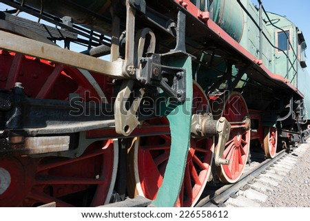 Partial view of a steam locomotive. Green metal boiler, red wheels, link motion, rods and drives, engineer's cab