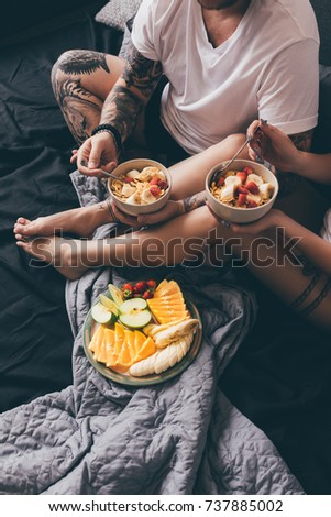 partial view of couple having healthy breakfast together in bed at home