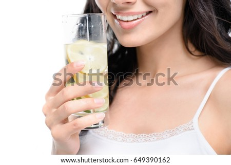 partial view of woman with glass of water near face isolated on white