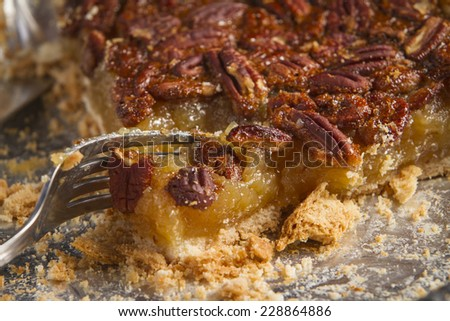 Partially eaten pre-made pecan pie being cut into by a fork.  - stock photo