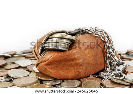 Partially opened purse with a few cents visible in it lies on other coins - stock photo