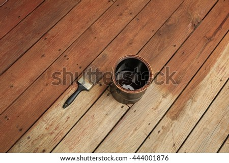 Partially stained deck; a paint brush and a can of stain dived treated and untreated areas - stock photo