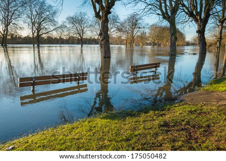 Partially submerged benches on a flooded riverbank in Windsor - stock photo
