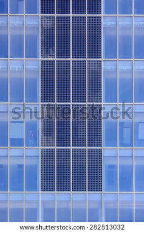 Partially transparent photovoltaic modules integrated on skyscraper - stock photo