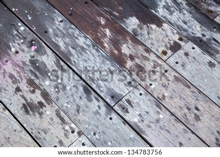 Partially wet wooden deck with screws, diagonal.