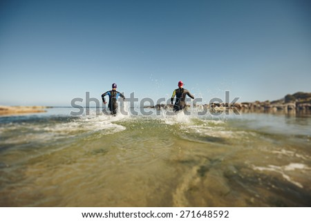Participants running into the water for start of a triathlon. Two triathletes rushing into water for swim portion of race. - stock photo