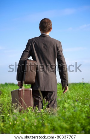Parting with old two suitcases in his hands the businessman in the field, seen from behind - stock photo