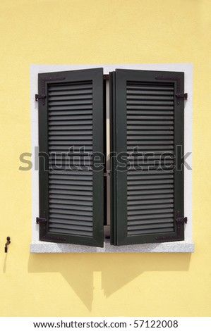 Partly opened green window shutters on bright yellow wall with great shadows - stock photo