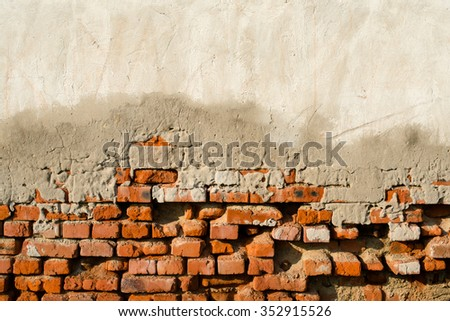 Partly plastered old brick wall with damped plaster, - stock photo