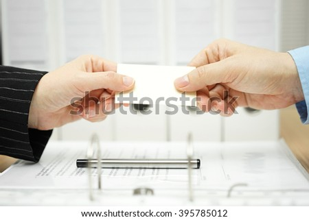 partners are exchanging business cards after successful meeting - stock photo