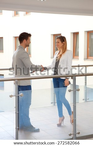 Partners meeting and shaking hands in corridor of apartment house. - stock photo