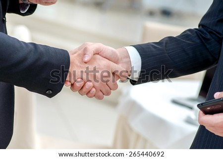 Partnership handshake. Two successful businessman standing in the restaurant and drink coffee while shaking hands with each other close-up view of hands